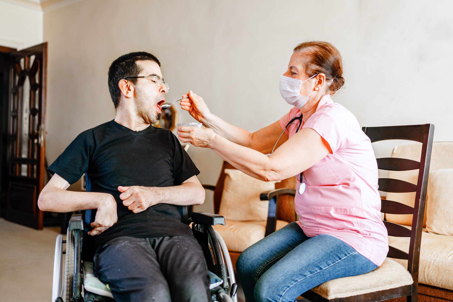 Serious disabled young man at home with nurse