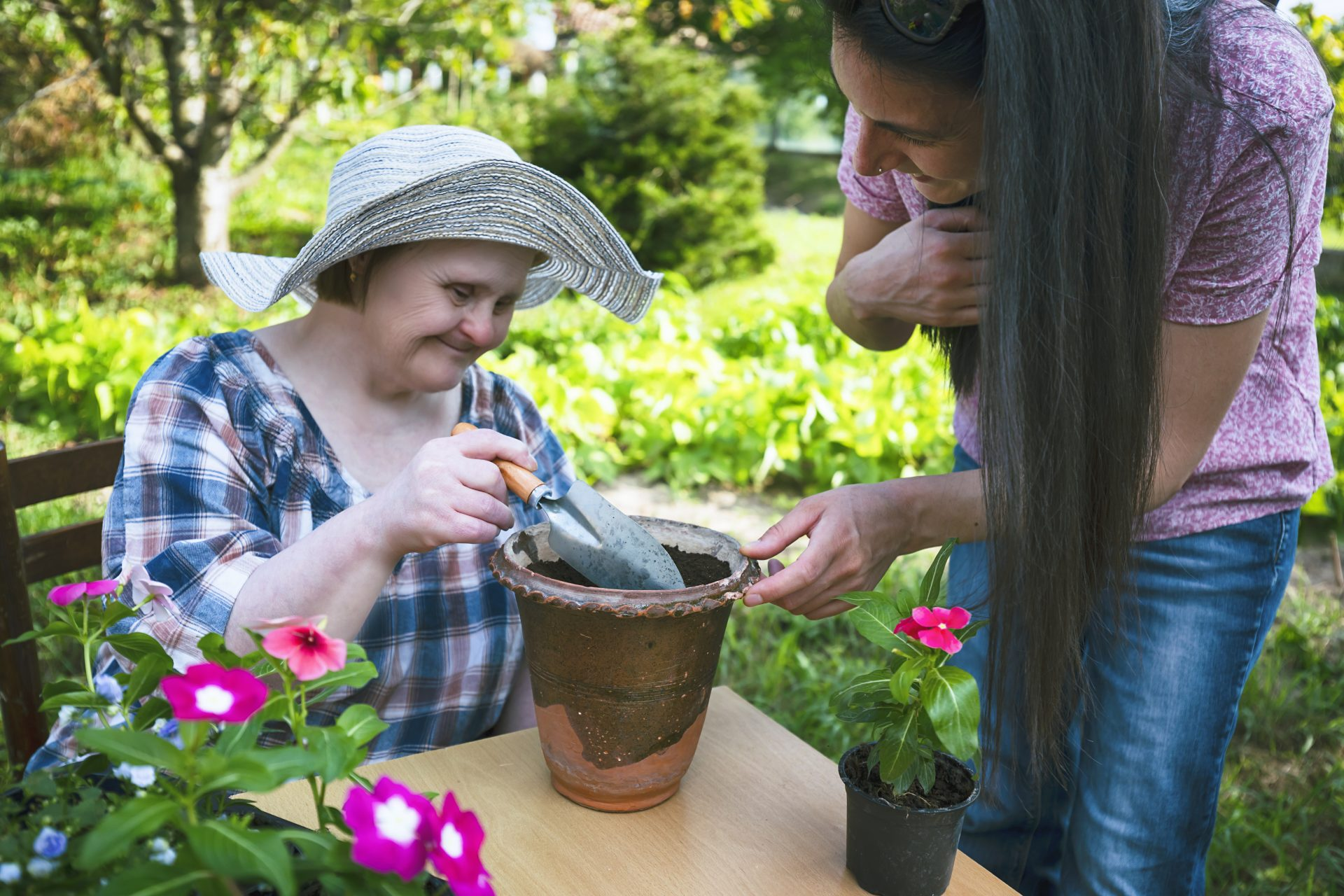Woman with Down Syndrome and her friend planting flowers together. Gardening.